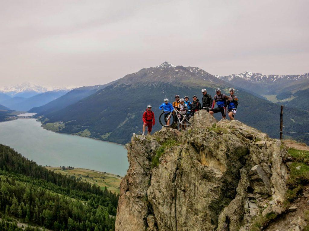 Mountainbiker auf einem Bergkamm, im Hintergrund Berge und Reschensee