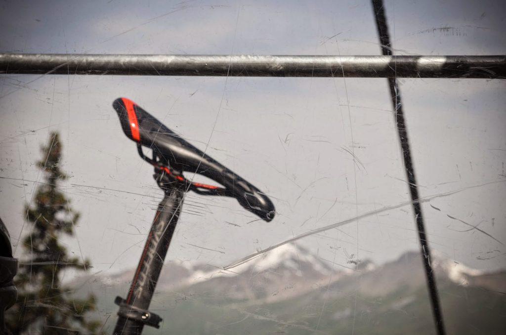 Blick auf Fahrradsattel und Bergpanorama durch Gondelfenster