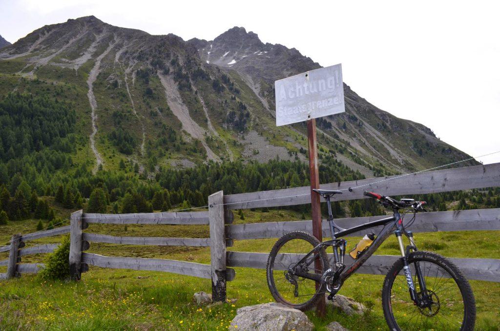 Mountainbike an Grenzzaun vor Berg